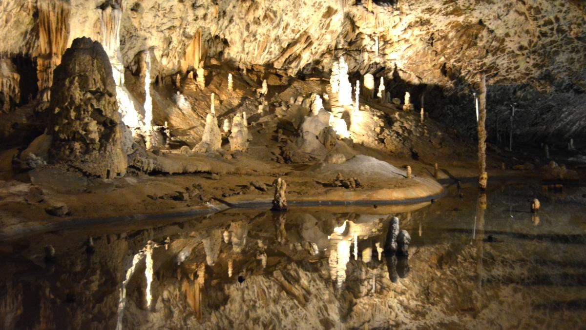 Stalagmiter och stalagtiter som speglar sig i en underjordisk sjö