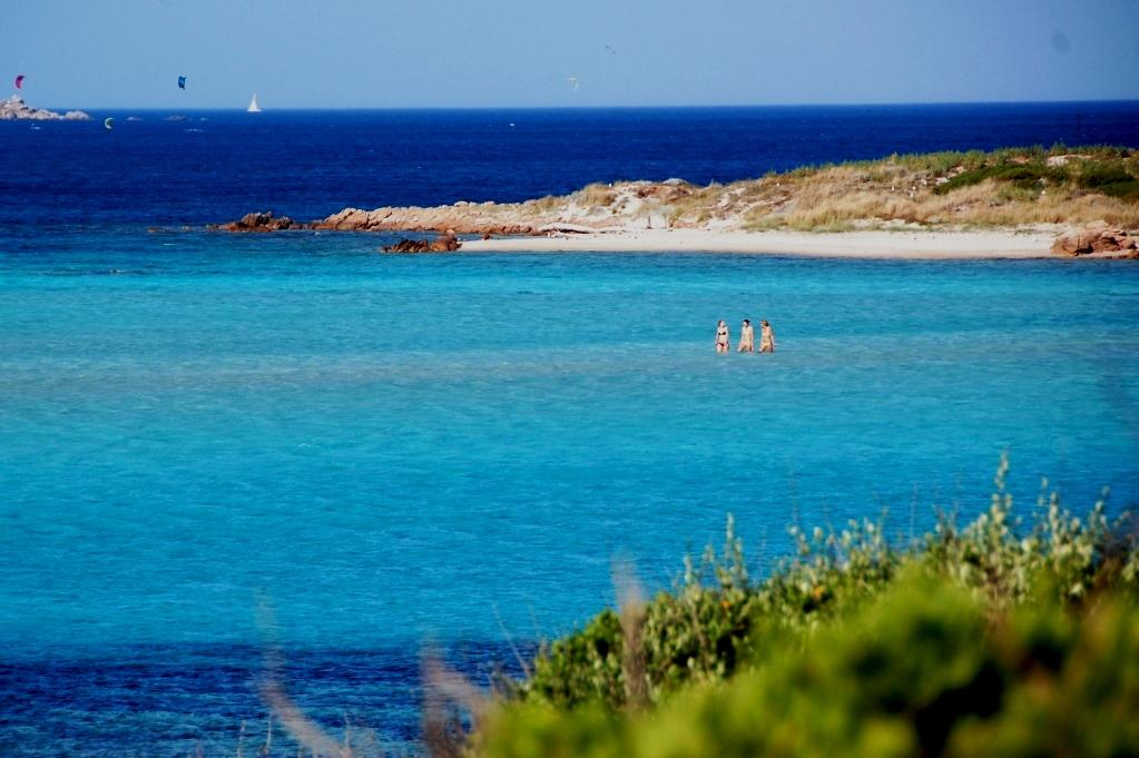 Tre tjejer vadar tillbaka från en av öarna utanför Sperone