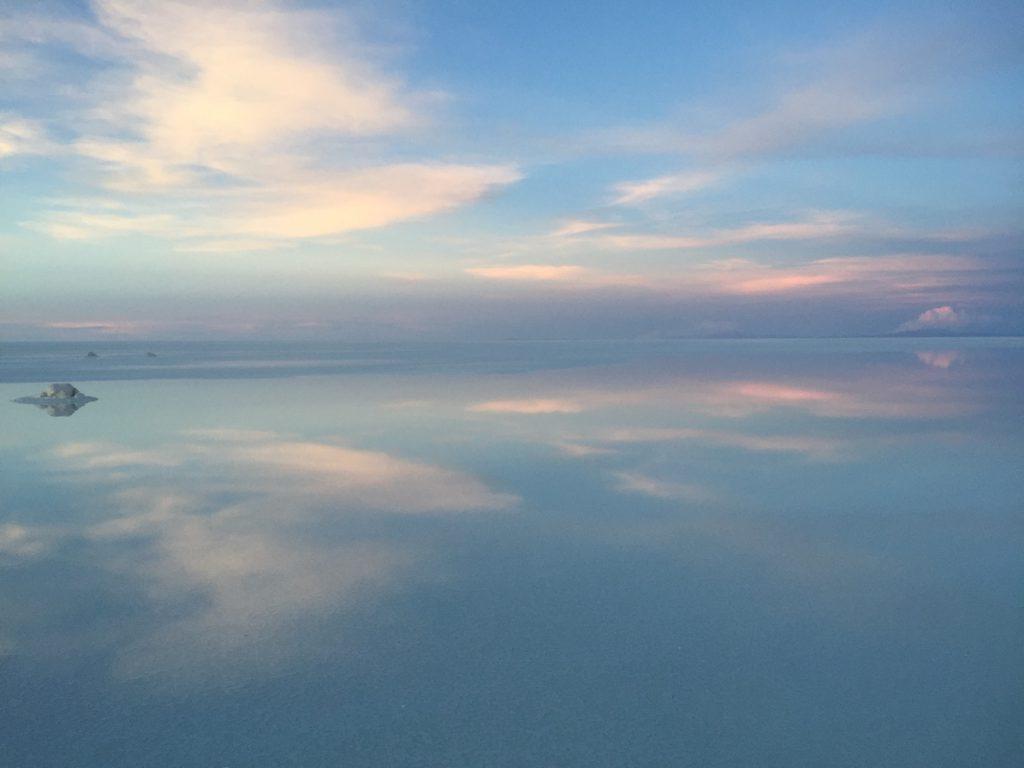 Solnedgång i Saltöknen i Bolivia, en magisk stund där himlen speglades i vattenytan på saltet