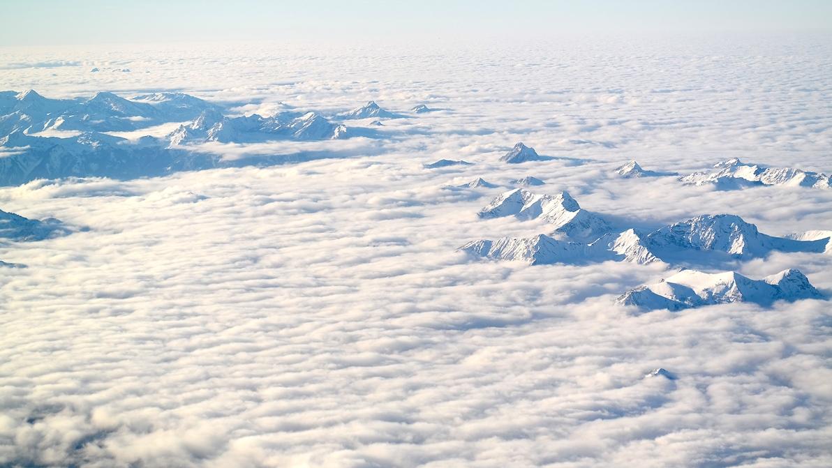Alperna sedda genom molnen, från flyget