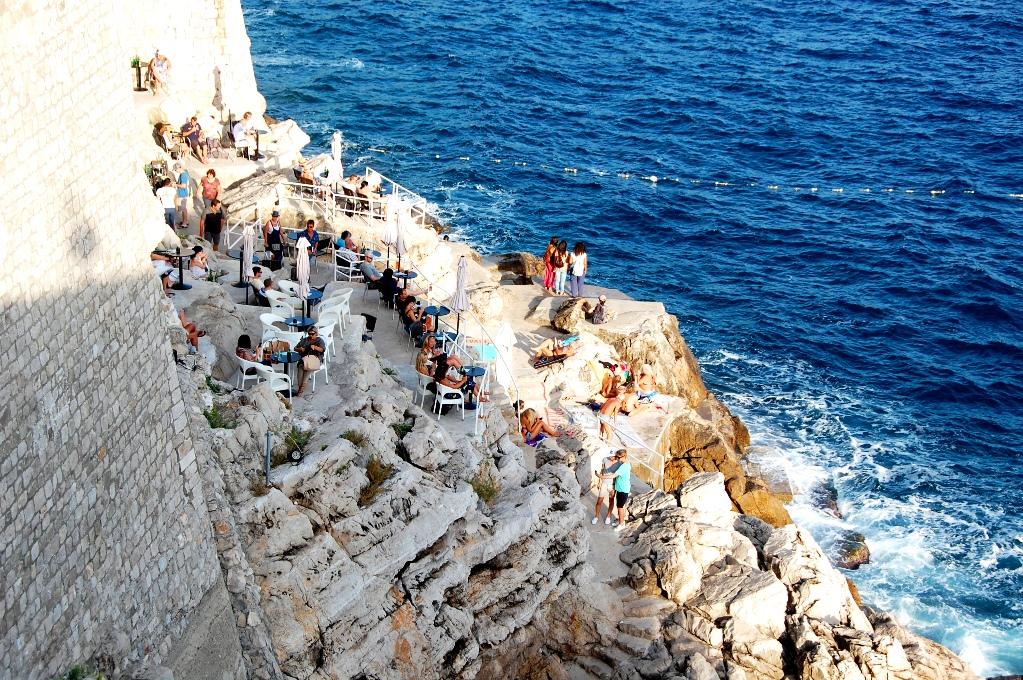 På en klippa utanför murarna sitter människor och solar
