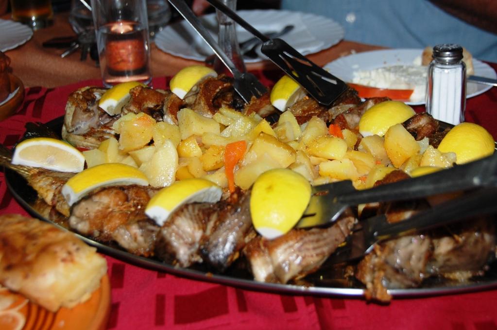Färsk fisk från fiskodlingen serverad med potatis och vitlökssås