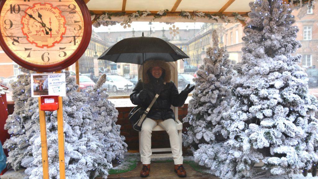 Peter med paraply, vid granar med konstgjord snö