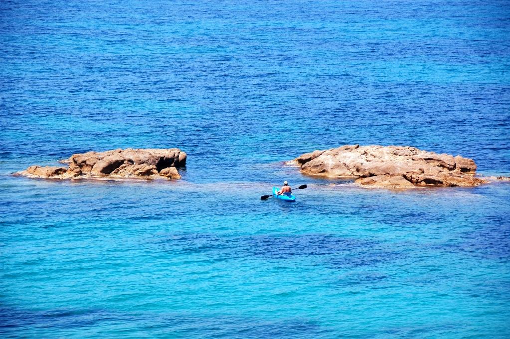 En blå kanot glider genom det blå vattnet