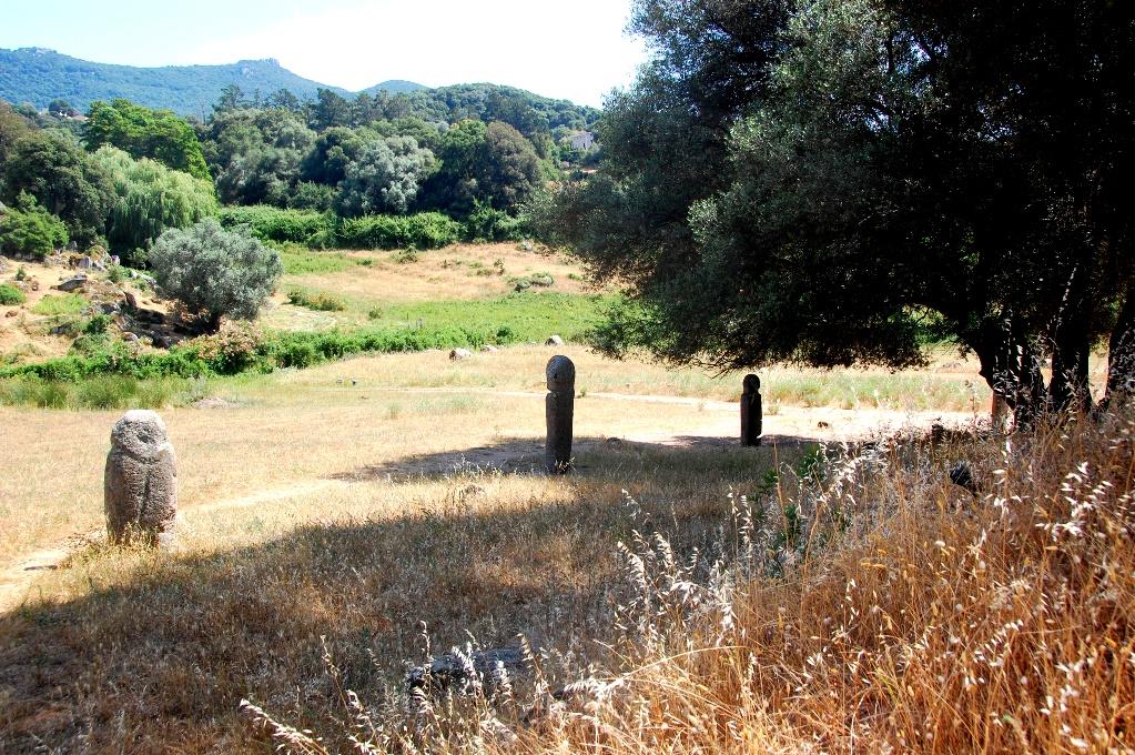 Urgamla stenstatyer i ring runt ett olivträd