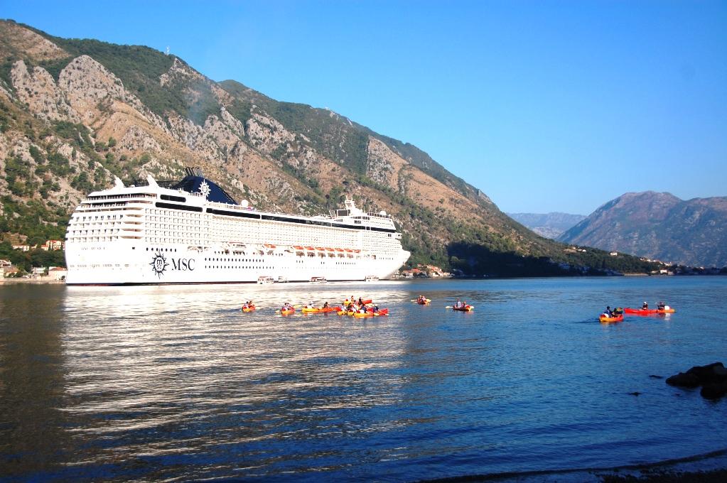 Stora och små båtar i bukten - kryssningsfartyg och kajaker