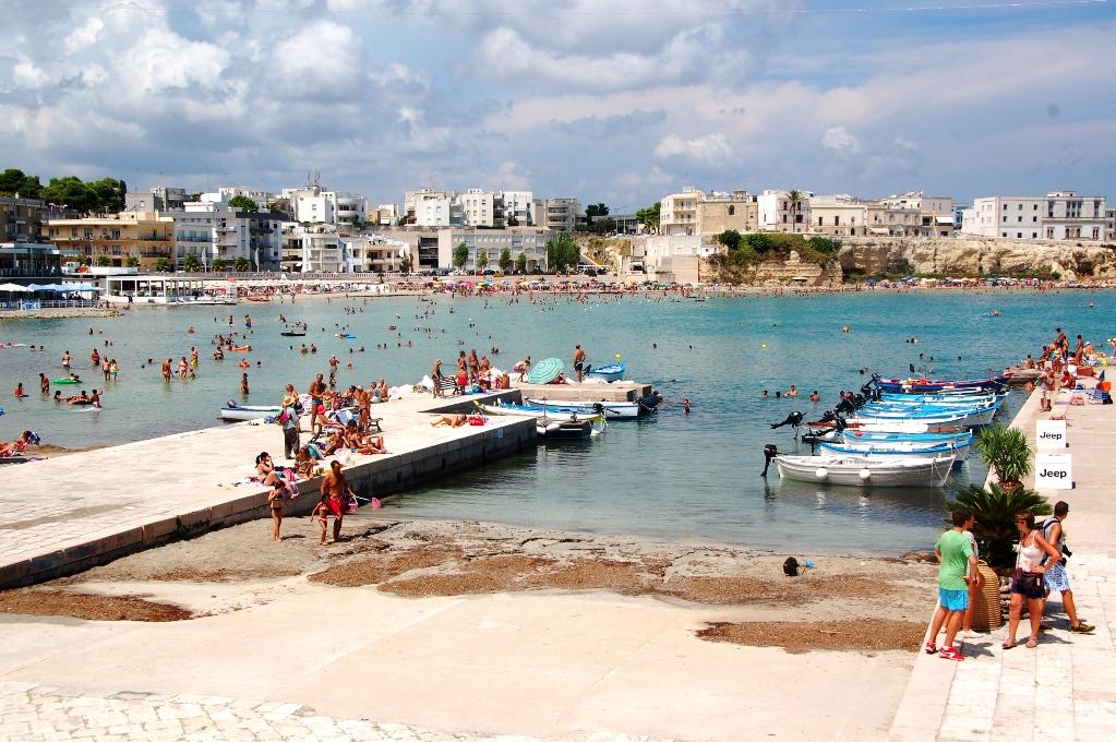 Många solar och badar vid klipporna mitt inne i Otranto
