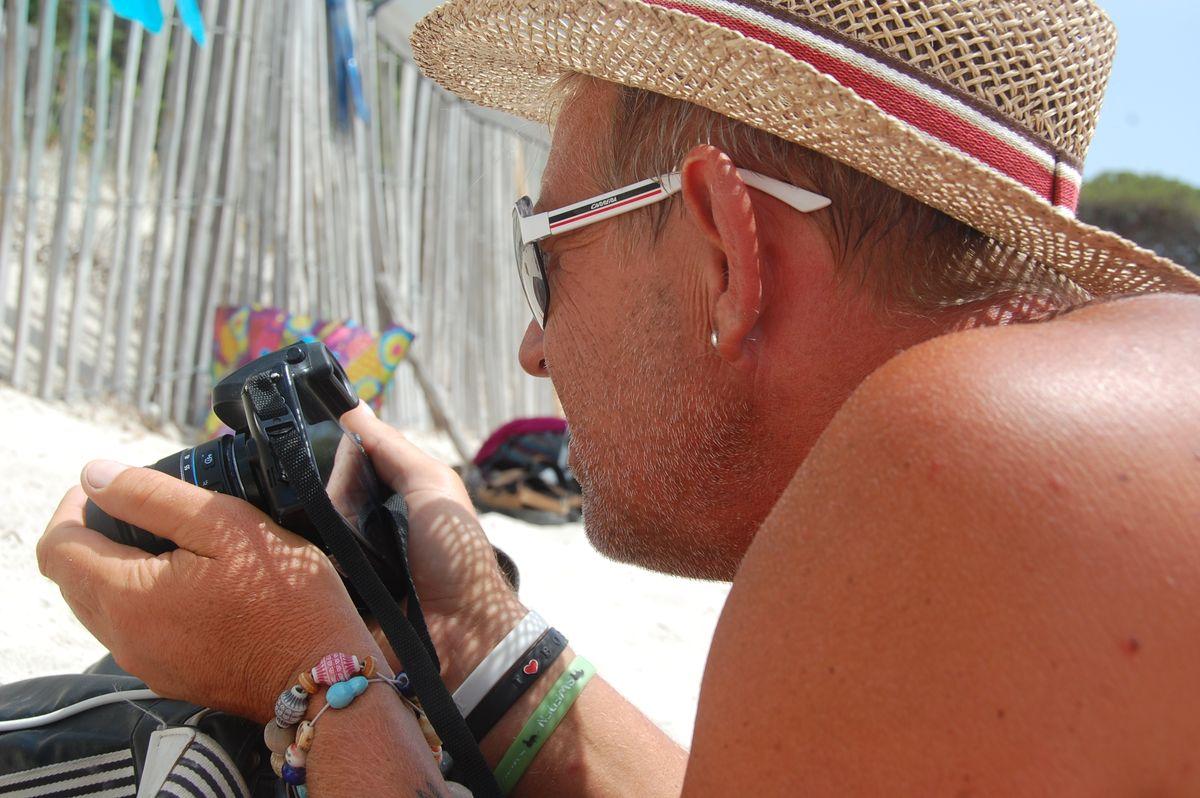 Peter ligger på stranden och kikar på dagens foton