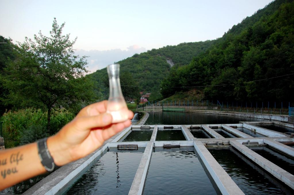 Peter håller upp ett glas raki (plommonbrännvin) framför restaurangens fiskodling