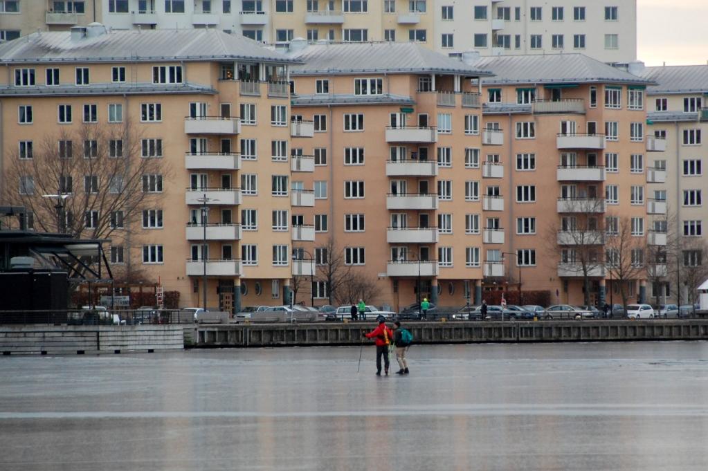 Vissa skridskoåkare åker nära husbåtarna, men dessa håller sig närmare Hornsbergs strand på Kungsholmen (andra sidan vattnet)