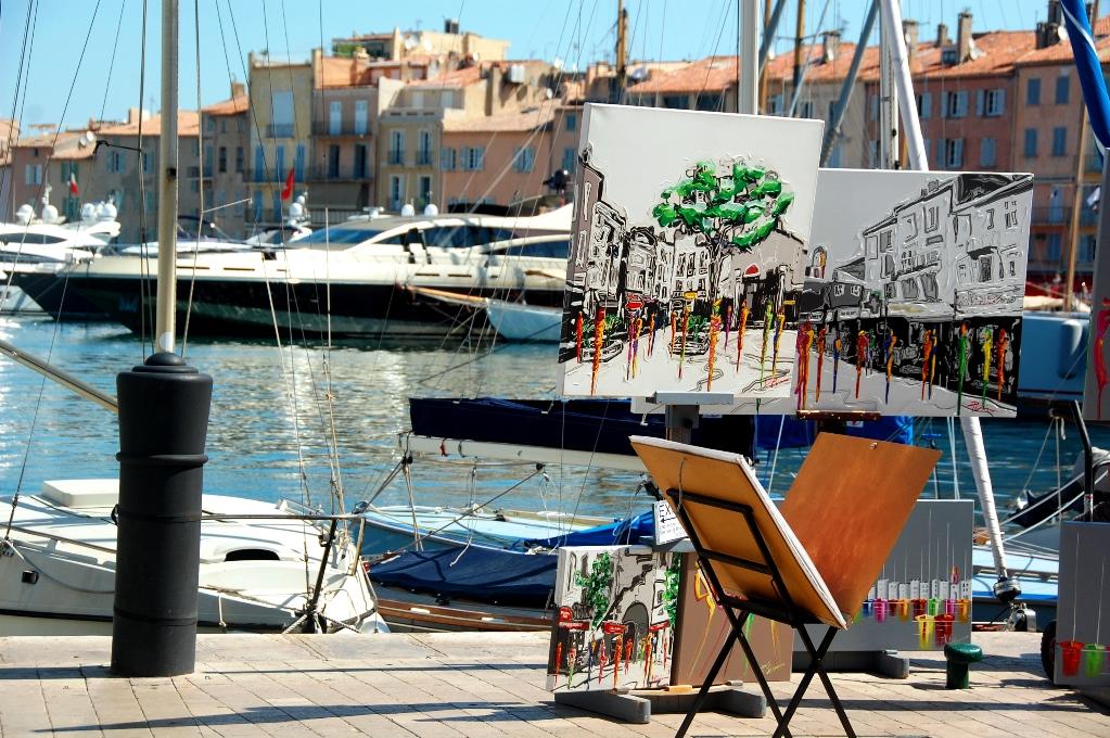 Vid hamnen står flera konstnärer och målar och säljer tavlor