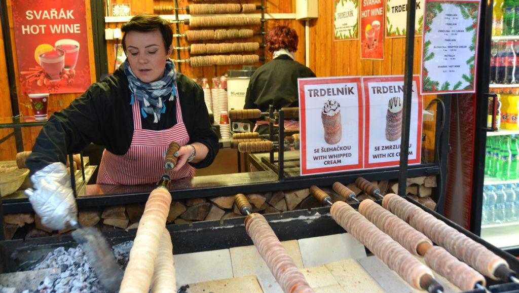 """En kvinna tar hand om tillagningen av bakverket """"trdelník"""""""