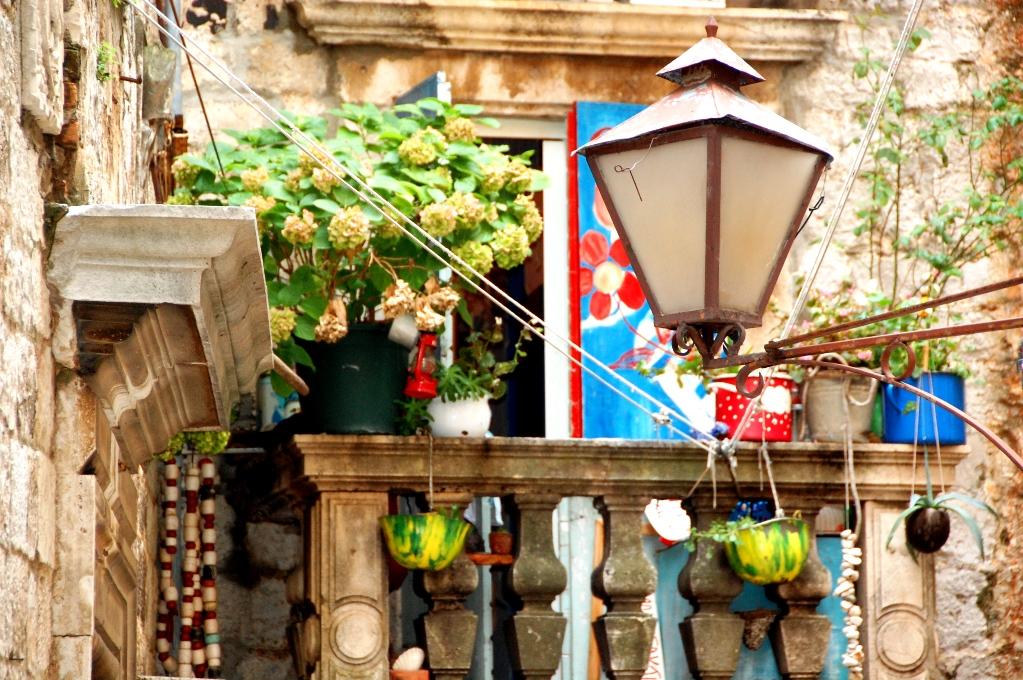 Den lite grå stadskärnan livas upp av växter och livfullt smyckade balkonger