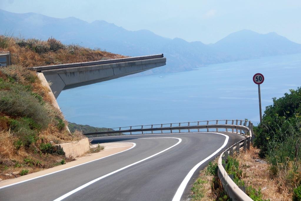 Slingrande vägar på Sardiniens västkust med överhäng som hindrar jord och sten att rasa över bilarna
